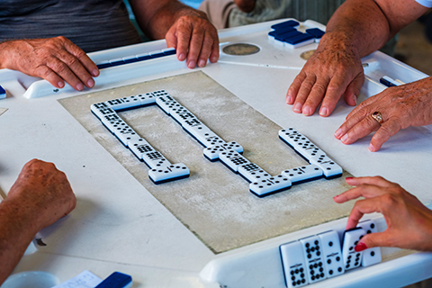 An up close stock photo of a game of dominos on Calle Ocho in Miami, Florida.