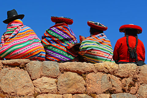 This is a stock photo. A Quechua family sitting on a ledge looking out.